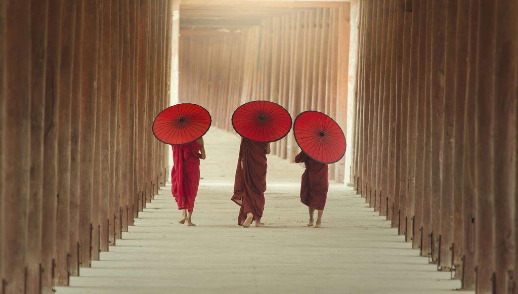 Drei junge buddhistische Mönche gehen einen Weg entlang